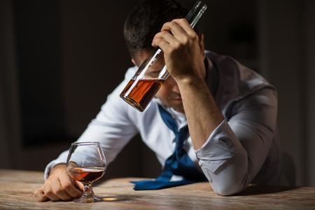 drunk man drinking alcohol at table at night Stock Photo