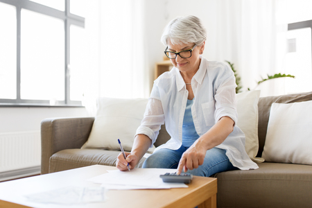 senior woman with money and bills at home Stock Photo