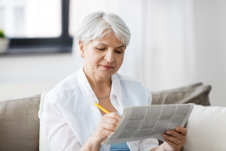 senior woman marking newspaper ad at home