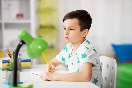 kleiner Junge, der zu Hause auf Notizbuch schreibt