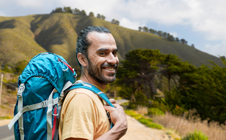 close up of man with backpack over big sur hills