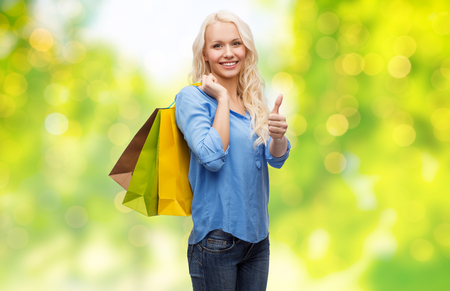 young woman with shopping bags showing thumbs up Stock Photo