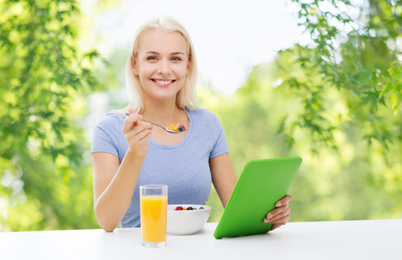 smiling woman with tablet pc eating breakfast Stock Photo