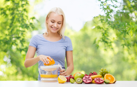 happy woman making fruit juice or orange fresh Stockfoto