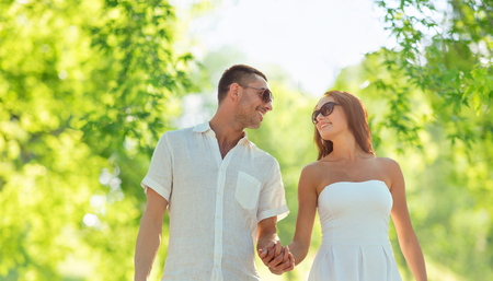 happy couple holding hands over natural background