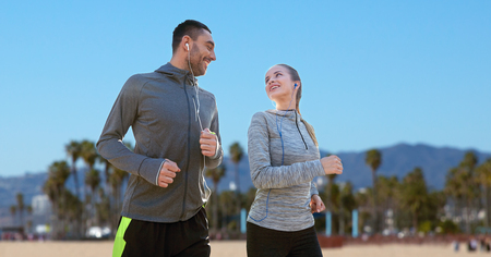 couple with earphones running over venice beach Stock Photo