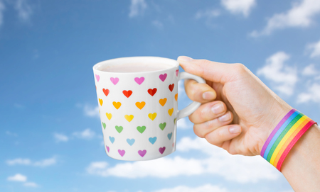 hand with cup of cacao and gay awareness wristband Archivio Fotografico