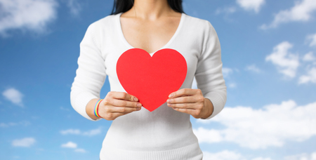 donna con il braccialetto di consapevolezza che tiene il cuore