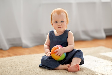 lovely redhead baby girl with toy ball at home