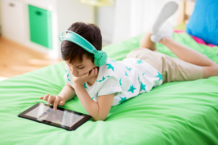 boy with tablet pc and headphones at home