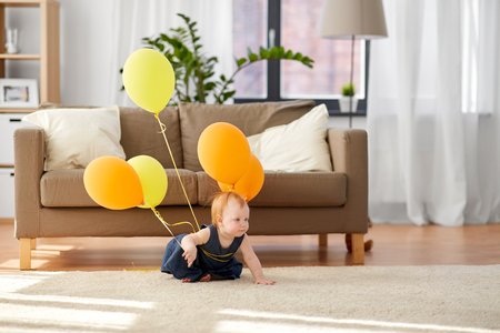 lovely redhead baby girl with balloons at home