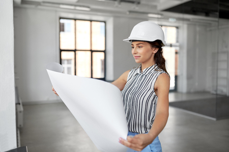 architect in helmet with blueprint at office room Stock fotó