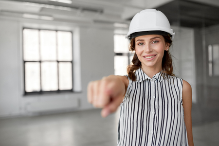 architect in helmet at office room pointing at you