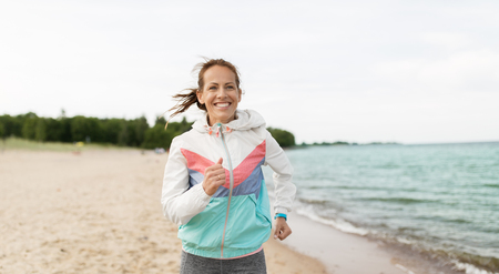 Woman with fitness tracker running along beach