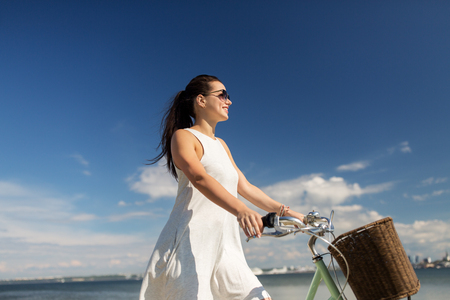 happy young woman with fixie bicycle at seaside Imagens