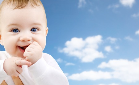 childhood and people concept - close up of sweet little baby over sky background Stock Photo