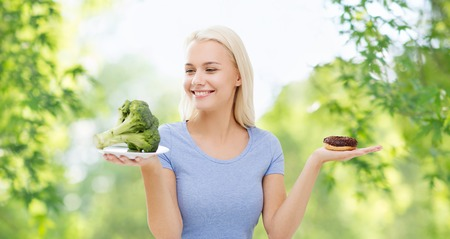 healthy eating, junk food, diet and choice people concept - smiling woman choosing between broccoli and donut over green natural background