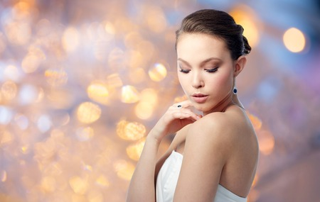 beauty, jewelry, people and luxury concept - beautiful asian woman or bride with earring and finger ring over holidays lights background Stock Photo