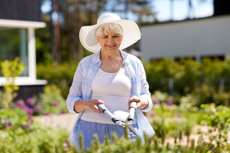 gardening, trimming and people concept - happy senior woman or gardener with hedge trimmer at summer garden
