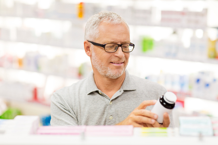 medicine, pharmaceutics, healthcare and people concept - senior male customer with drug at pharmacy Reklamní fotografie