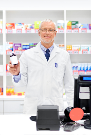 medicine, healthcare and people concept - senior apothecary with drug at pharmacy cash register Stock Photo