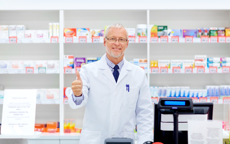 medicine, healthcare and people concept - senior apothecary at pharmacy cash register showing thumbs up