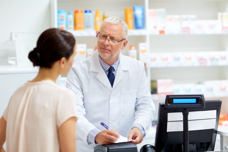 medicine, healthcare and people concept - senior apothecary writing prescription for female customer at pharmacy Stock Photo