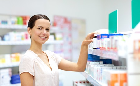 medicine, pharmaceutics, healthcare and people concept - female customer choosing drugs at pharmacy