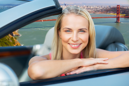 woman in convertible car over golden gate