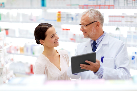 apothecary and customer with tablet pc at pharmacy Stock Photo