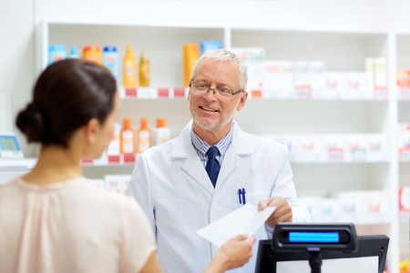 senior apothecary with prescription at pharmacy