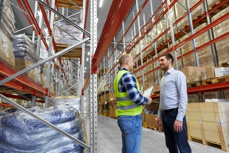 worker with clipboard and businessman at warehouse