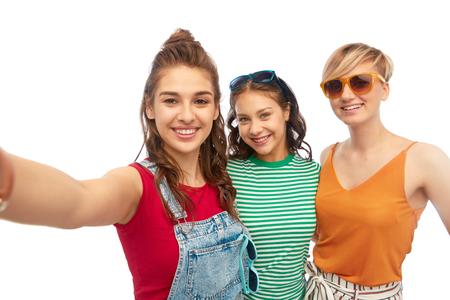 happy female friends in sunglasses taking selfie