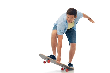 smiling young man riding skateboard over white