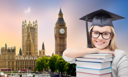 graduate in mortarboard with books over london