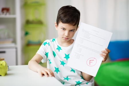 sad boy holding school test with f grade