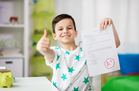 happy smiling boy holding school test with a grade
