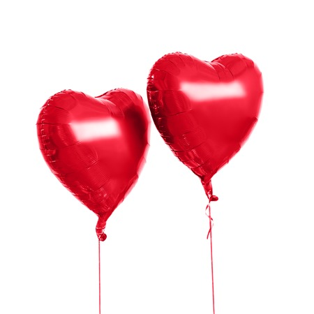holidays, valentines day and party decoration concept - two red helium inflated heart shaped balloons over white background