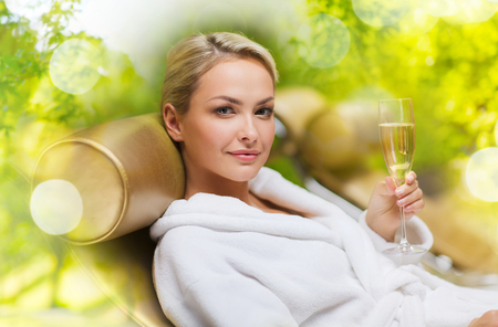 spa, leisure and luxury concept - beautiful woman in white bath robe lying on chaise-longue and drinking champagne over green natural background Stock Photo