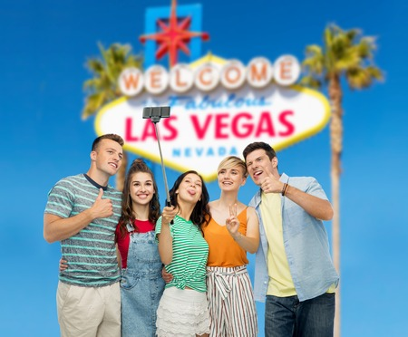 entertainment, leisure and technology concept - group of happy smiling friends taking selfie by smartphone over welcome to fabulous las vegas sign background Stock fotó