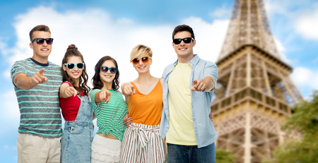 travel, tourism and summer holidays concept - group of happy smiling friends in sunglasses hugging pointing at you over eiffel tower background