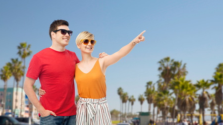 travel, tourism and summer holidays concept - smiling couple in sunglasses hugging and pointing finger to something over venice beach background in california