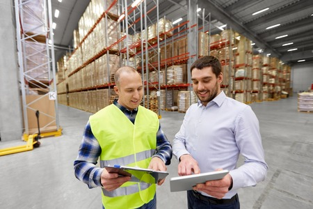 logistic business, shipment and people concept - warehouse worker and businessman with clipboard and tablet pc computer Фото со стока