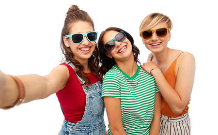friendship and people concept - group of happy female smiling friends in sunglasses taking selfie over white background