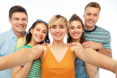 happy friends taking selfie over white background Stock Photo