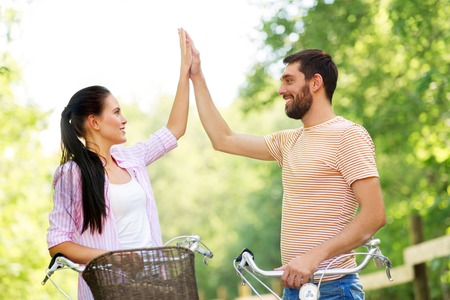 couple with bicycles making high five in summer