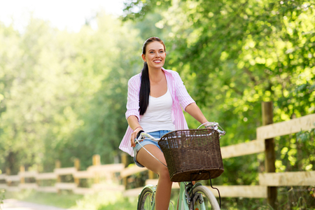 woman riding bicycle with basket at summer park Imagens