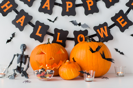 holidays and decoration concept - jack-o-lantern or carved pumpkins with candies and happy halloween garland on white background