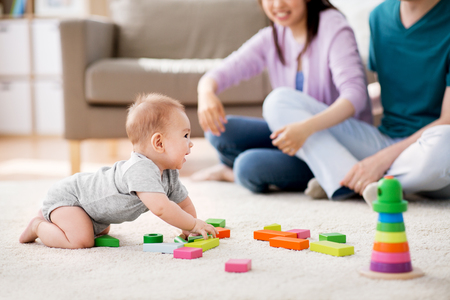 family, parenthood and people concept - happy mother, father and baby boy playing toy blocks at home Imagens