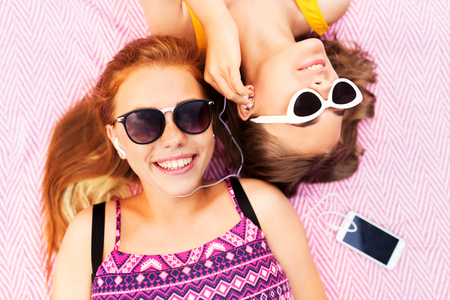 summer fashion, leisure and technology concept - smiling teenage girls in sunglasses and earphones lying on picnic blanket and listening to music from smartphone 版權商用圖片